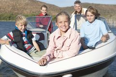 Caucasian Family Of Five In Speedboat. Portrait of a happy Caucasian family of five in speedboat on lake royalty free stock photos