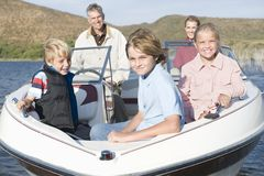 Caucasian Family Of Five In Speedboat. Portrait of a happy Caucasian family of five in speedboat on lake royalty free stock images
