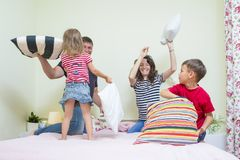 Caucasian Family of Four Having a Playful Funny Pillow Fight Royalty Free Stock Photography