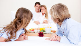 Caucasian family having breakfast sitting on bed Royalty Free Stock Photo