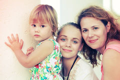 Caucasian family, mother with two daughters. Outdoor summer evening portrait of a real Caucasian family, young mother with her two daughters, colorful toned Royalty Free Stock Photo