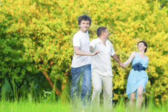 Caucasian Family of Three Having Fun Together and Running in Summer Forest With Joined Hands. Stock Photo