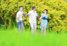 Caucasian Family of Three Having Fun Together and Running in Summer Forest With Joined Hands. Royalty Free Stock Photos