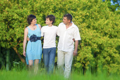 Caucasian Family of Three Having a Walk Together in Park Embraced Royalty Free Stock Photography