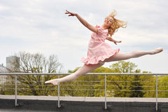 Caucasian fashion ballerina leaping on the roof Stock Image
