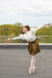 Caucasian fashion ballerina leaping on the roof Royalty Free Stock Images