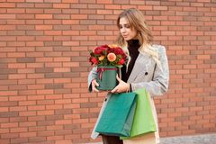 Caucasian fashion woman standing on the street near storefront shop windows holding flower-box with happy smile stock image