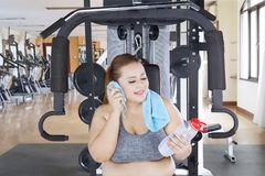 Caucasian fat woman resting in the gym center. Caucasian fat woman holding a bottle of water while resting after a workout in the gym center Stock Image