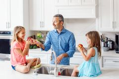 Free Caucasian Father Dad Gives Children Daughters Fresh Fruits To Eat Stock Images - 150551314