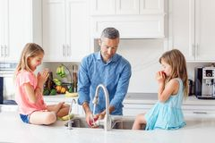 Caucasian father dad gives children daughters fresh fruits to eat