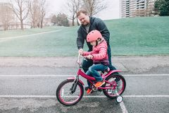 Caucasian father dad training helping girl daughter to ride bicycle. royalty free stock image