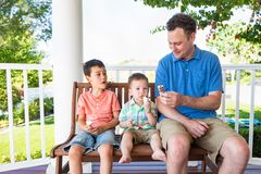 Caucasian Father Eating Ice Cream With His Mixed Race Chinese Sons stock image