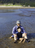 Caucasian father playing in water on beach with disabled son Royalty Free Stock Photos