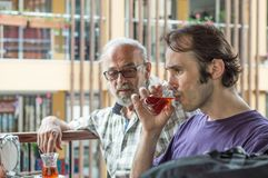 Turkish men sitting at the cafe and drinking red Turkish tea. Caucasian father and son sitting at the cafe, drinking Turkish tea Stock Photos