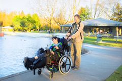 Father walking with disabled son in wheelchair at lake park stock photo