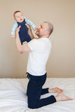 Caucasian father in white t-shirt and black jeans sitting on bed indoors, holding taking up newborn baby son. Portrait of middle age Caucasian father in white t stock images