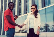 Caucasian female and black man handshake. Caucasian female and black men handshake in a town Royalty Free Stock Photography