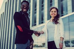 Caucasian female and black man handshake. Caucasian female and black men handshake in a town Royalty Free Stock Image