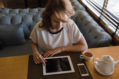 Caucasian female browsing website pages on touch pad while breakfast in modern coffee shop Stock Photo