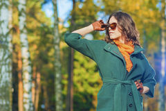 Caucasian Female Brunette Model Posing in Autumn Forest with Sun. Glasses. Horizontal Image Composition stock photo