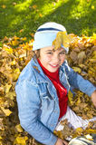 Caucasian female child playing in autumn leaves Royalty Free Stock Photography