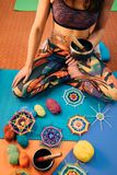 Meditation with knitting mandala in class. Caucasian female in a colorful outfit with henna tattoo on her side sitting on a mat in a lotus position holding stock images