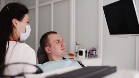 Caucasian female dentist in white robe, mask and black gloves explaining x-ray image on the black screen to male patient. Shows the image of unhealthy tooth to stock video footage
