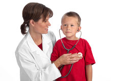 Caucasian female doctor giving boy a physical. Female caucasian doctor giving a cute blond boy a physical, letting him listen to his own heart Royalty Free Stock Images