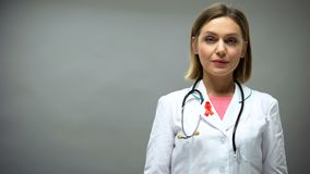 Caucasian female doctor with red ribbon, international HIV AIDS awareness sign royalty free stock photo