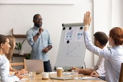 Young caucasian employee interrupts african american male mentor giving presentation stock photo