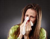Caucasian female with flu blowing her nose Stock Photography