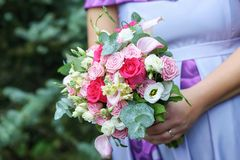 Caucasian female guest or bridesmaid wearing a lilac summer dress which shows a lovely baby bump and holding a wedding bouquet stock photos