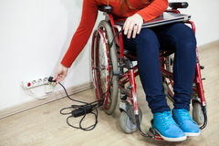 Caucasian female hand stretching to power socket in wall. Disabled woman in wheelchair Royalty Free Stock Photos