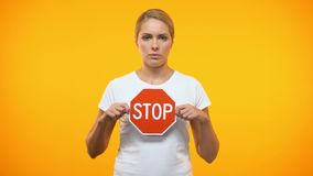 Caucasian female holding stop sign in hands, restriction symbol, warning danger. Stock footage stock video