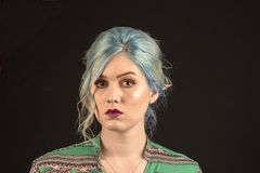 Caucasian female model, Age 22, Blue dyed hair, Red lips, green and red shirt. Isolated on black background. Head and shoulders stock image