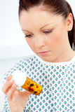 Caucasian female patient looking at pills Royalty Free Stock Image