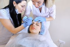 Caucasian female person visiting professional dermatologist and cosmetologist for permanent makeup. Caucasian female person visiting professional cosmetologist stock photography