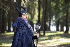 Caucasian Female Poses in Maleficent Clothing and Horns in Spring Forest. Holding Crook with Mirror Ball. Horizontal Image stock photography