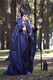 Caucasian Female Poses in Maleficent Clothing and Horns in Spring Forest. Holding Crook with Mirror Ball. Vertical Image royalty free stock image