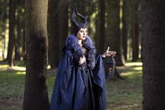 Caucasian Female Poses in Maleficent Clothing and Horns in Spring Forest. Holding Lamp in Hand. Horizontal Image stock images