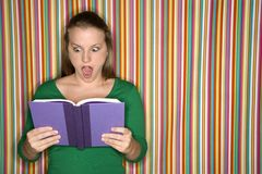 Caucasian female reading book making expression. Stock Photography