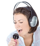 Caucasian female singing into microphone. Stock Photography
