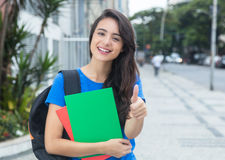 Caucasian female student with blue shirt showing thumb in the city Royalty Free Stock Image