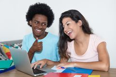 Caucasian female student learning with african american male stu. Dent at desk at home Stock Photography