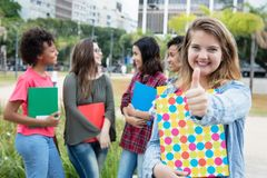 Caucasian female student showing thumb with group of internation. Al students outdoors on campus of university Stock Images