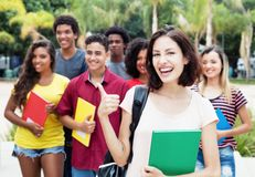 Caucasian female student showing thumb with group of internation. Al students outdoor in the summer in the city Stock Image