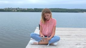 Caucasian female watching at tablet while sitting near lake stock video footage