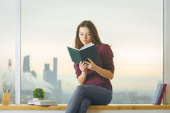 Caucasian female on windowsill reading book Royalty Free Stock Photography