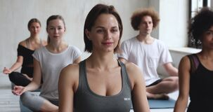 Caucasian female yoga coach and multiracial people meditating indoors