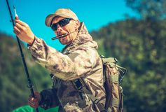 Fisherman with Knife in Mouth. Caucasian Fisherman in His 30s with Knife in Mouth Preparing For a Fly Fishing royalty free stock photography